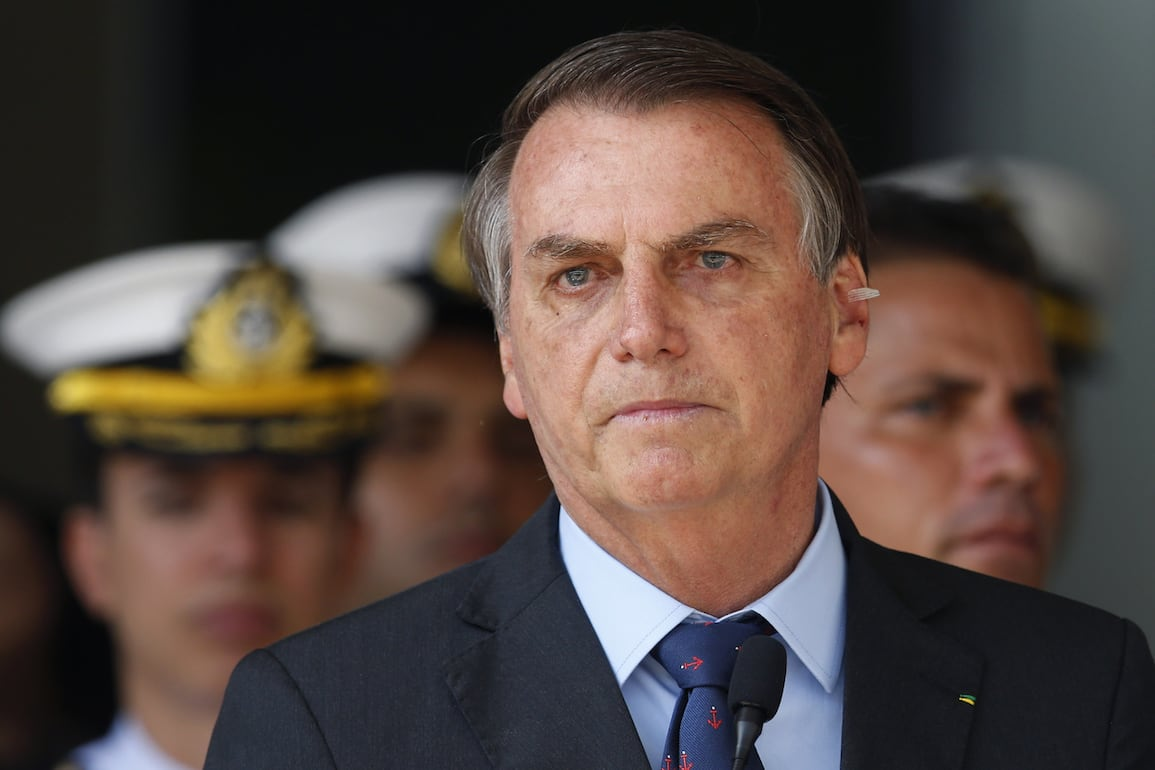 FILE - In this Dec. 13, 2019 file photo, with a band aid on his ear where a mole was removed, Brazil's President Jair Bolsonaro attends a military ceremony in honor of Sailor Day, in Brasilia, Brazil. Bolsonaro left a hospital on Tuesday morning, Dec. 24 after a fall in the presidential residence. (AP Photo/Eraldo Peres, File).Jair Bolsonaro