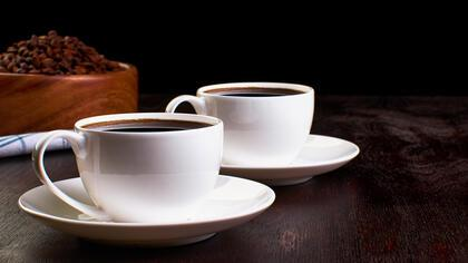 Two cups of coffee in saucers on a dark wooden table. In the background, a wooden dish with coffee beans on a tea towel.