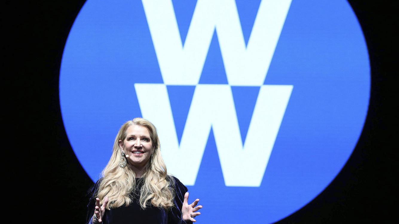 FILE- In this Feb. 7, 2018, file image distributed for Weight Watchers, Weight Watchers President and Chief Executive Officer Mindy Grossman speaks at a global employee event in New York. Weight Watchers is trimming its name to just two letters: WW. The company says it is renaming itself to focus more on overall wellness and not just dieting. (Amy Sussman/AP Images for Weight Watchers, File)
