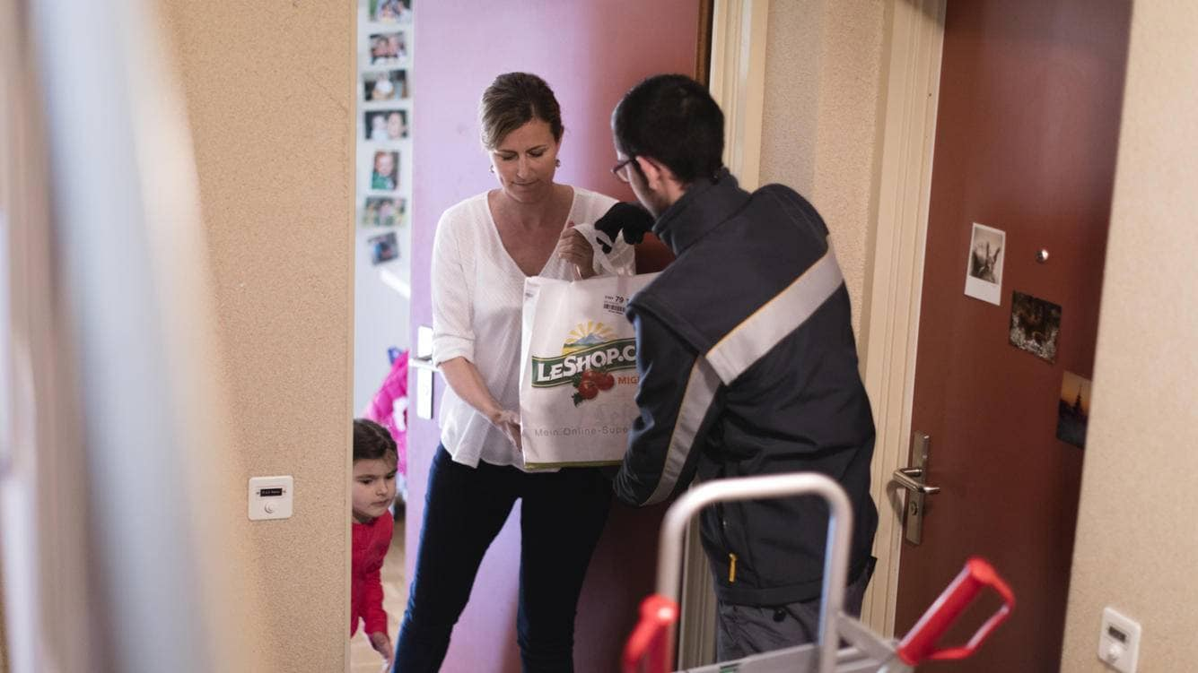A postal employee hands over a LeShop.ch delivery to a woman and her child in an apartment building in Thalwil in the canton of Zurich, Switzerland, on March 17, 2016. LeShop.ch is a Swiss online supermarket which was founded in 1997. (KEYSTONE/Gaetan Bally)