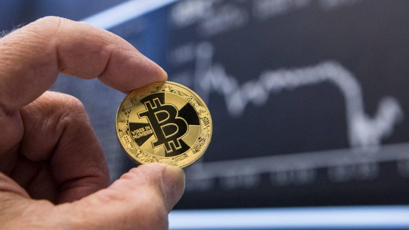 GERMANY, FRANKFURT - SEPTEMBER 28: Symbol photo on the topics digital curreny, cryptocurrency, currency speculation, stock market, etc. The picture shows a Bitcoin  (coin physically) in front of the course blackboard of the German Stock Exchange in Frankfurt.  (Photo by Ulrich Baumgarten via Getty Images)