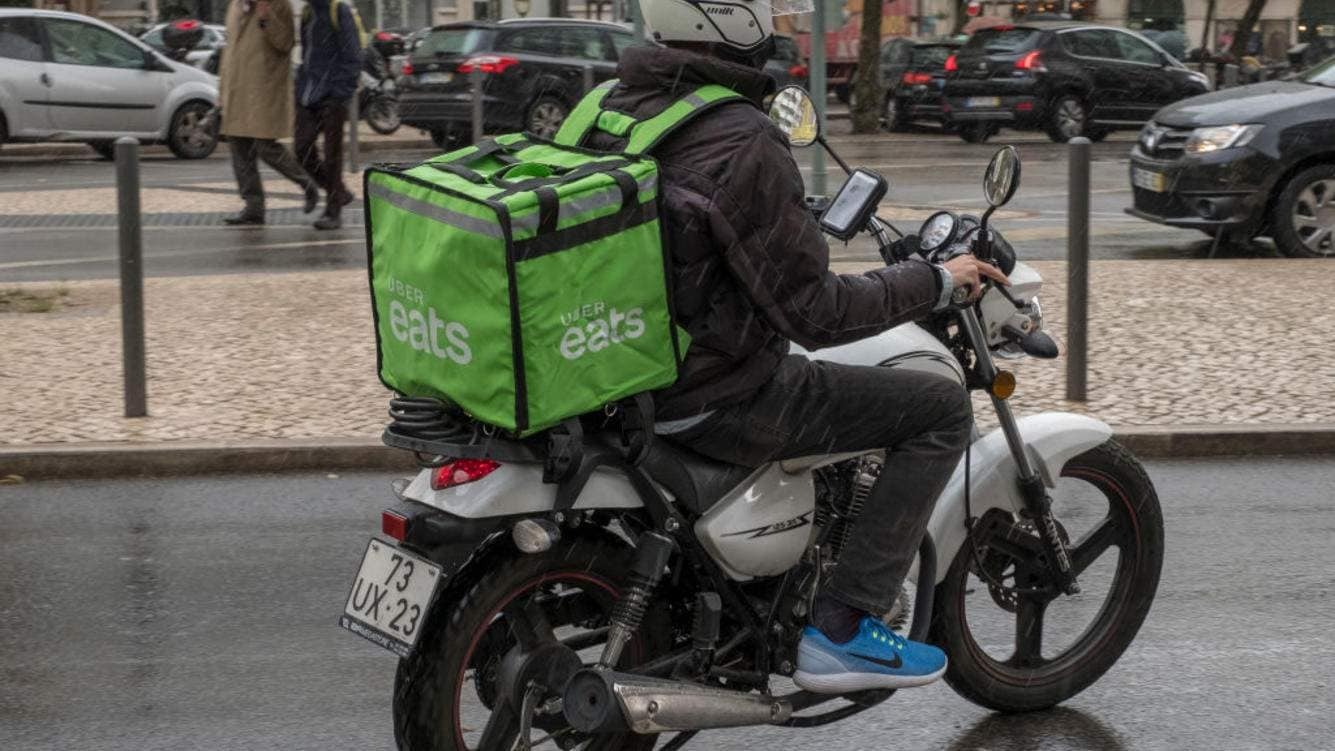 LISBON, PORTUGAL - OCTOBER 30: Uber Eats driver rides his motorcycle  in the rain on his way to a delivery on October 30, 2018 in Lisbon, Portugal. The free, standalone Uber Eats app allows customers to order meals and Uber Eats drivers to deliver food from affiliated local eateries. Food prices are set by the participating restaurants and Uber Eats adds a booking fee based primarily on the distance between the eatery and the customer. (Photo by Horacio Villalobos - Corbis/Corbis via Getty Images)