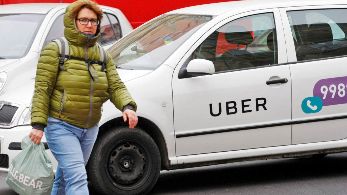 KIEV, UKRAINE - 2018/10/20: A woman seen walking next to a white car with a logo of Uber taxi cab company in Kiev, Ukraine. (Photo by Pavlo Conchar/SOPA Images/LightRocket via Getty Images)