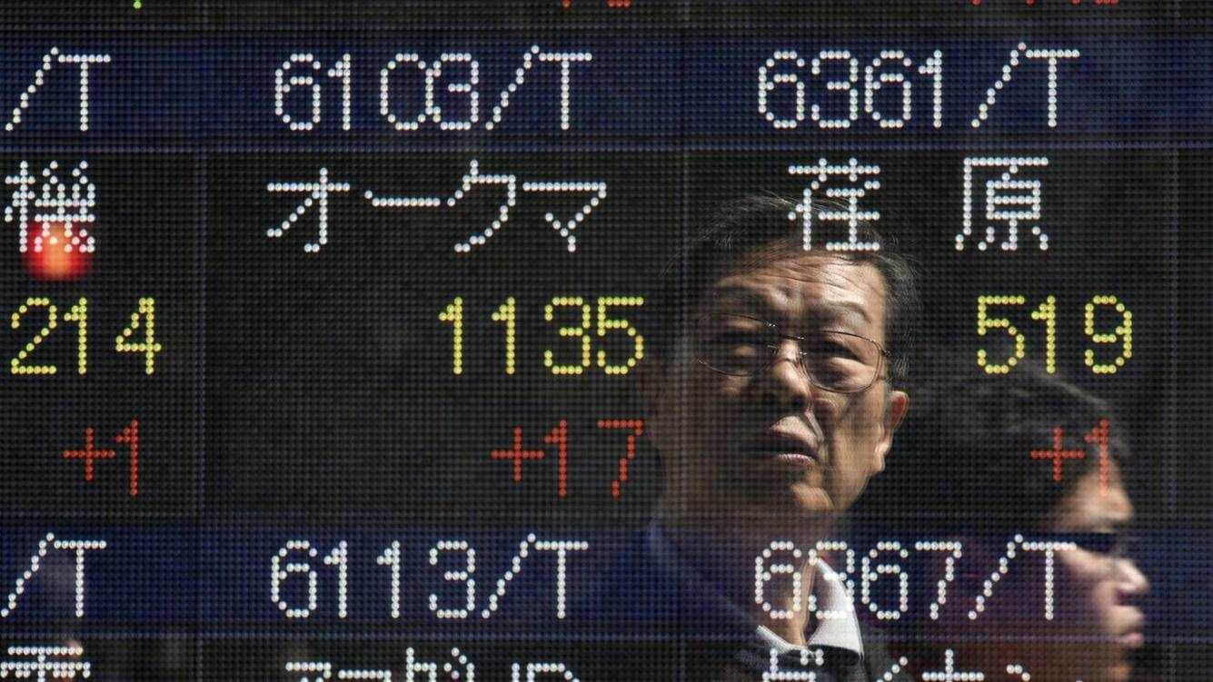 epa04696503 A passerby is reflected on a stock market indicator board in Tokyo, Japan, 09 April 2015. The 225-issue Nikkei index ended up 147.91 points, or 0.75 per cent, to close at 19,937.72, its highest since April 2000.  EPA/FRANCK ROBICHON
