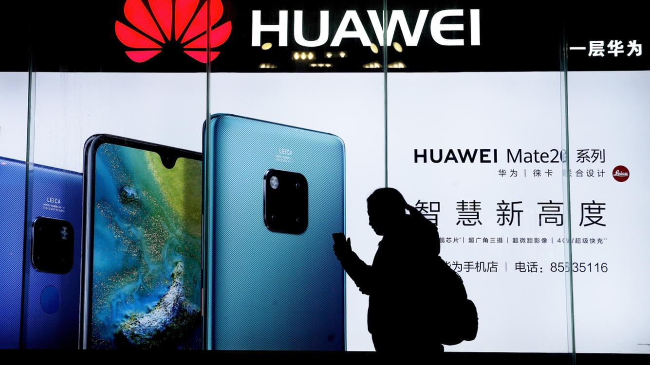 FILE - In this Dec. 11, 2018, file photo, a woman browses her smartphone as she walks by a Huawei store at a shopping mall in Beijing. China has called on the United States to 'stop the unreasonable crackdown' on Huawei following the tech giant's indictment on charges of stealing technology, violating trade sanctions and lying to banks. (AP Photo/Andy Wong, File)