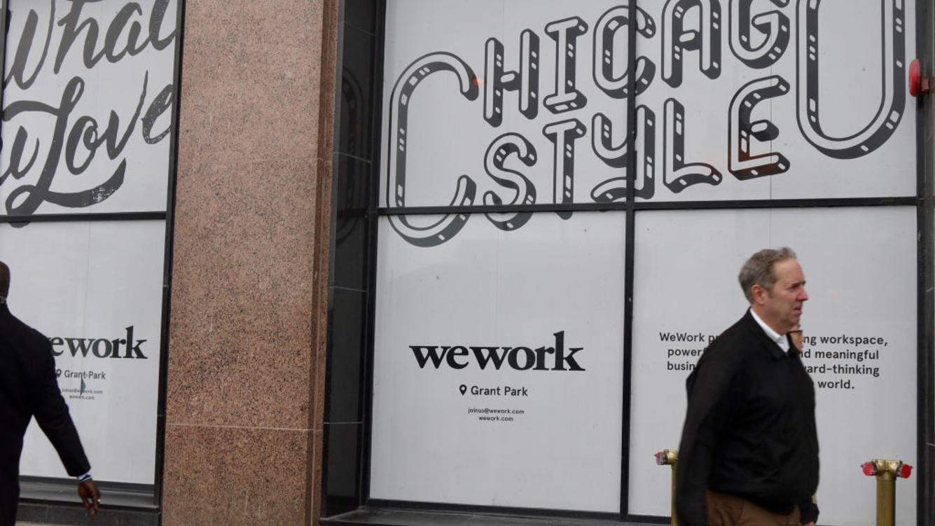 View of pedestrians walking by a storefront sign for the workspace sharing company WeWork near Grant Park at 332 South Michigan Avenue in Chicago, Illinois, October 28, 2018. (Photo by Interim Archives/Getty Images)