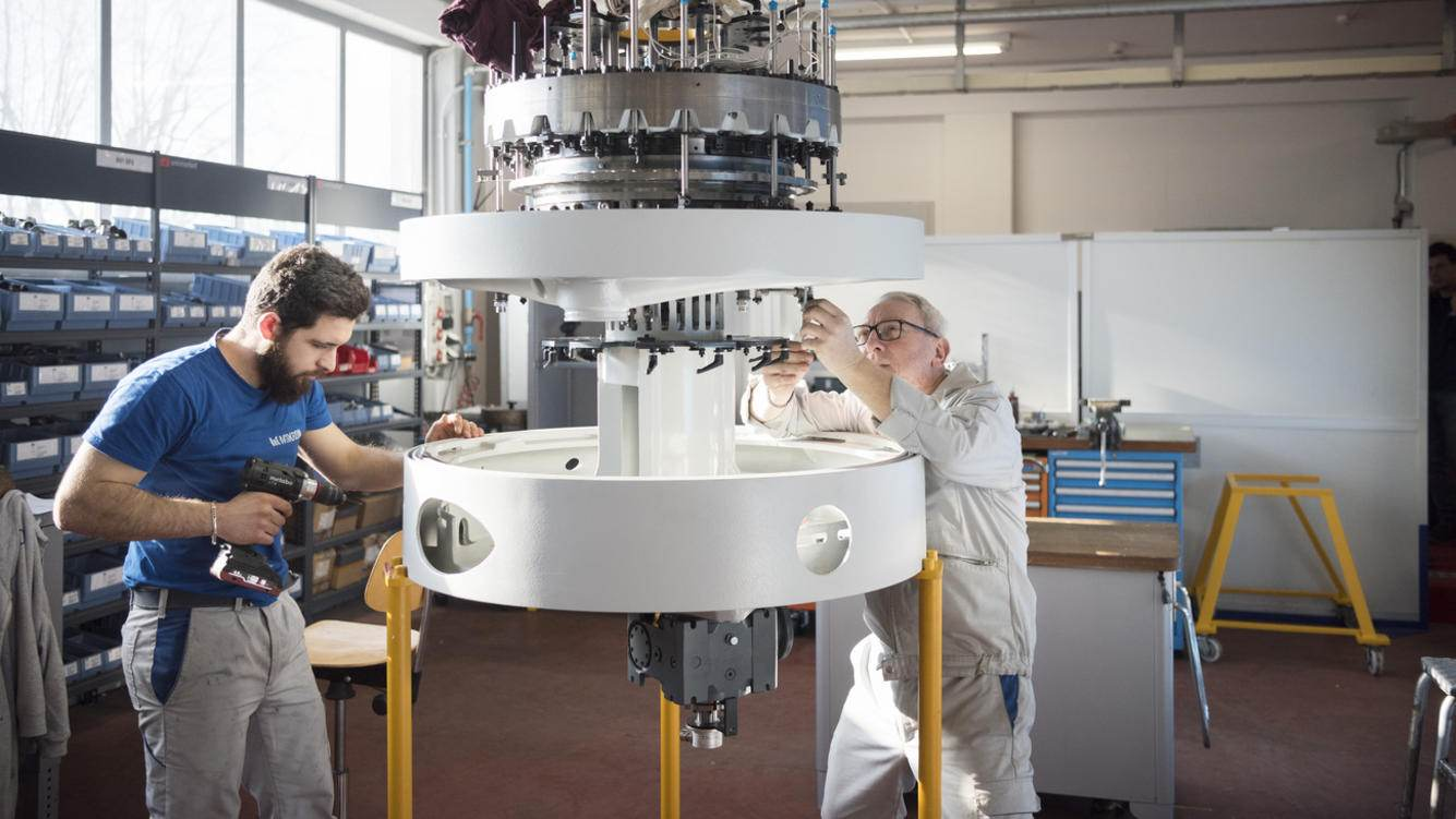 Employees work on a machine at the Mikron Machining production site of the Mikron Group in Agno, Canton of Ticino, Switzerland, on January 24, 2019. The engineering company Mikron Group develops, produces and markets automation solutions as Mikron Automation in Boudry, Canton of Neuchatel, as well as machining systems as Mikron Machining and cutting tools, as Mikron Tool, in Agno, besides various production sites abroad. (KEYSTONE/Christian Beutler)