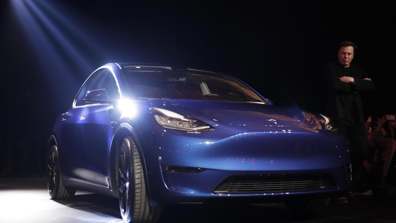 Tesla CEO Elon Musk, right, stands next to the Model Y at Tesla's design studio Thursday, March 14, 2019, in Hawthorne, Calif. The Model Y may be Tesla's most important product yet as it attempts to expand into the mainstream and generate enough cash to repay massive debts that threaten to topple the Palo Alto, Calif., company. (AP Photo/Jae C. Hong)
