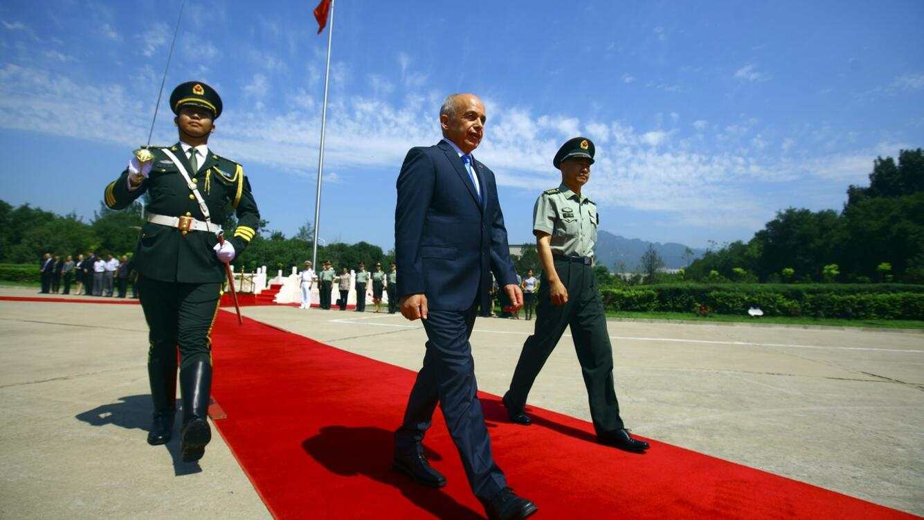 epa03790448 Swiss President and Defense Minister Ueli Maurer (C) and Su Rong (R), Commander of the 6th Armored division of the PLA (People's Liberation Army)walk on the red carpet during a welcome ceremony at an army training facility on the outskirts of Beijing, China, 17 July 2013. Maurer visited a PLA training facility during his visit to China.  EPA/DIEGO AZUBEL
