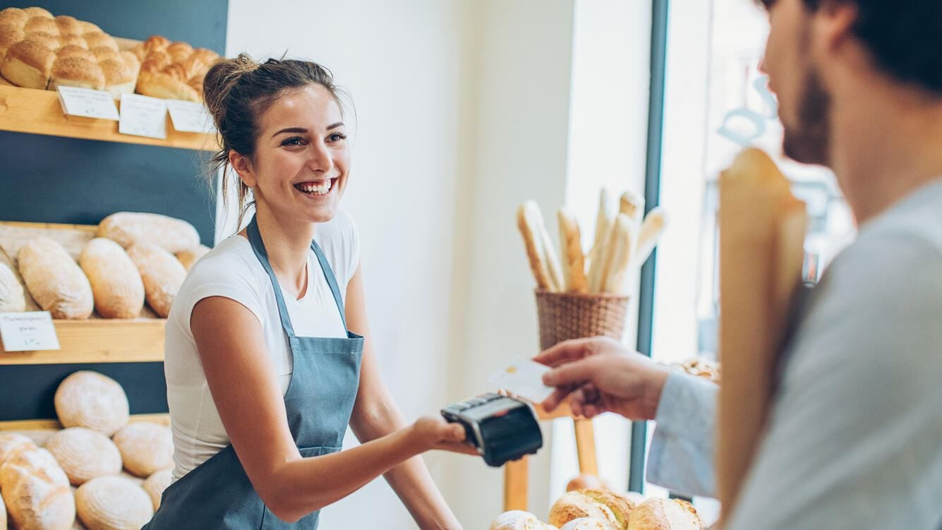 Customer making a credit card payment in a bakery