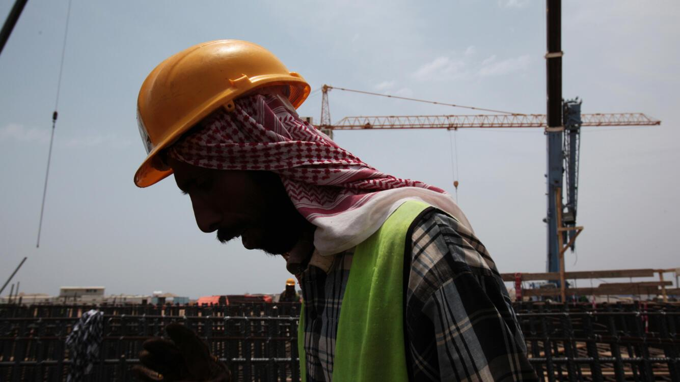 In this photo taken May 8, 2014, an Asian man works on construction of the Kingdom Tower, a planned 252-story building, which aims to become the world's tallest skyscraper when complete, in Jiddah, Saudi Arabia. Prince Alwaleed bin Talal's Kingdom Holding Company and the construction giant Saudi Binladin Group are among the owners of the project. The tower will house a luxury hotel, apartments and office space. (AP Photo/Hasan Jamali)