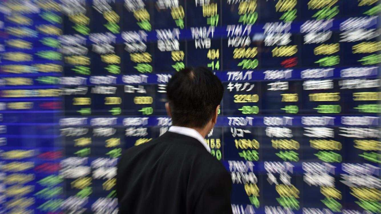 epa04455693 A pedestrian looks at a stock market indicator board in Tokyo,