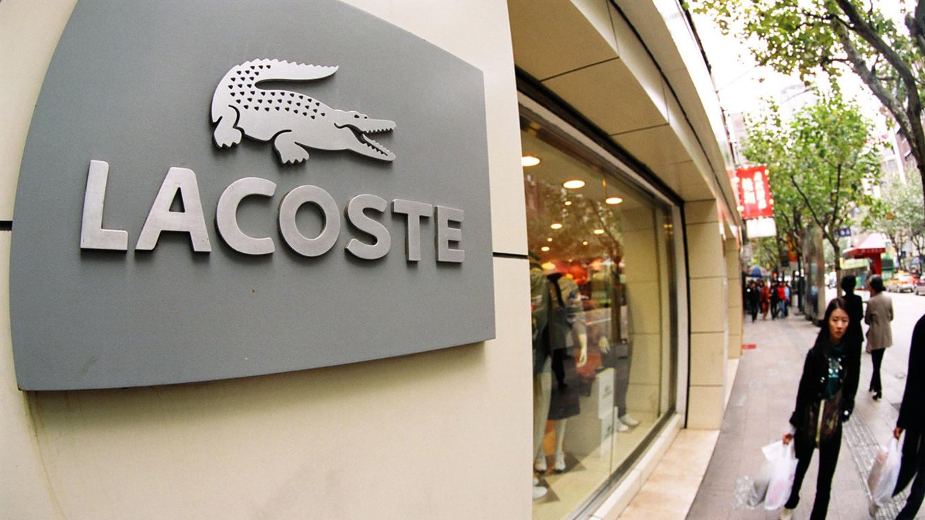 Locals walk past a Lacoste boutique in Shanghai.