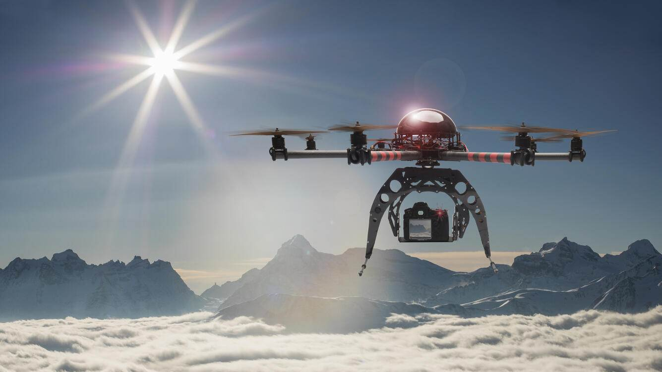 A drone flying and taking pictures over a sea of fog in the Alps