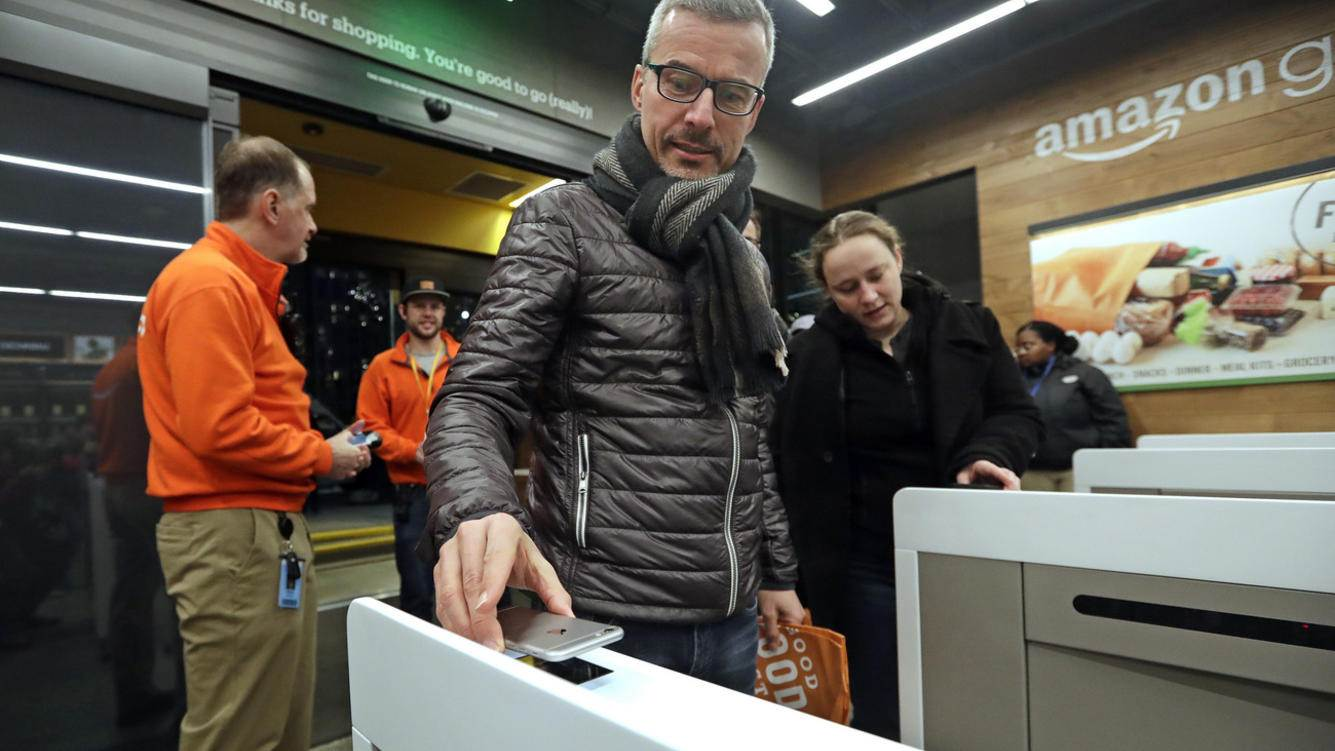 A customer scans his Amazon Go cellphone app at the entrance as he heads into an Amazon Go store, Monday, Jan. 22, 2018, in Seattle. The store, which opened to the public on Monday, allows shoppers to scan their smartphone with the Amazon Go app at a turnstile, pick out the items they want and leave. The online retail giant can tell what people have purchased and automatically charges their Amazon account. (AP Photo/Elaine Thompson)