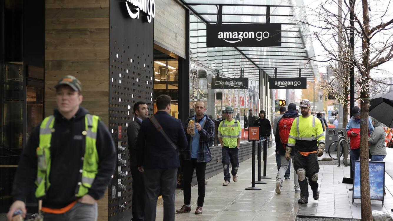 In this Nov. 9, 2018 photo, construction workers mix with the noon lunch-hour crowd outside an Amazon Go store in downtown Seattle.  As Amazon turns its attention to setting up new homes in Long Island City in New York  and Arlington, Va., experts and historians in Seattle say both places can expect a delicate relationship with the world's hottest online retailer.  (AP Photo/Ted S. Warren)