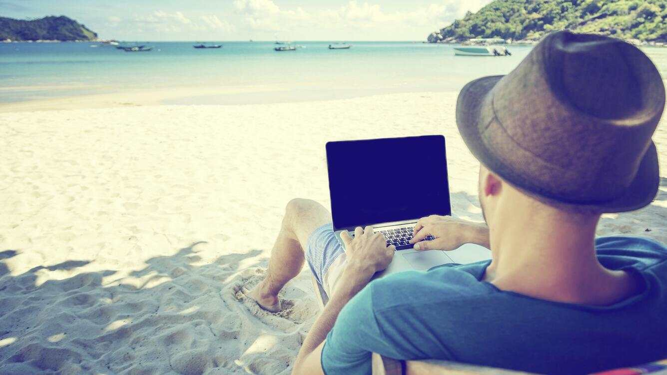 Attractive young man with laptop working on the beach. Freedom, remote work, freelancer, technology, internet, travel and vacation concepts