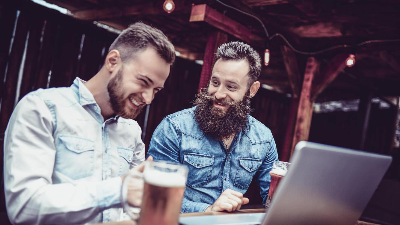 Freelancing Businessmen Drinking Beer And Working Together In A Bar