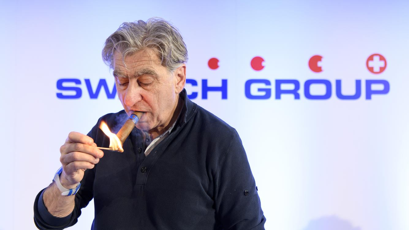 Nick Hayek, CEO Swatch Group, President of the Swatch Group Executive Management Board lights his cigar during a press conference of the year 2017 final results of Swiss watch company Swatch Group, in Biel, Switzerland, this Wednesday, March 14, 2018. (KEYSTONE/Anthony Anex)