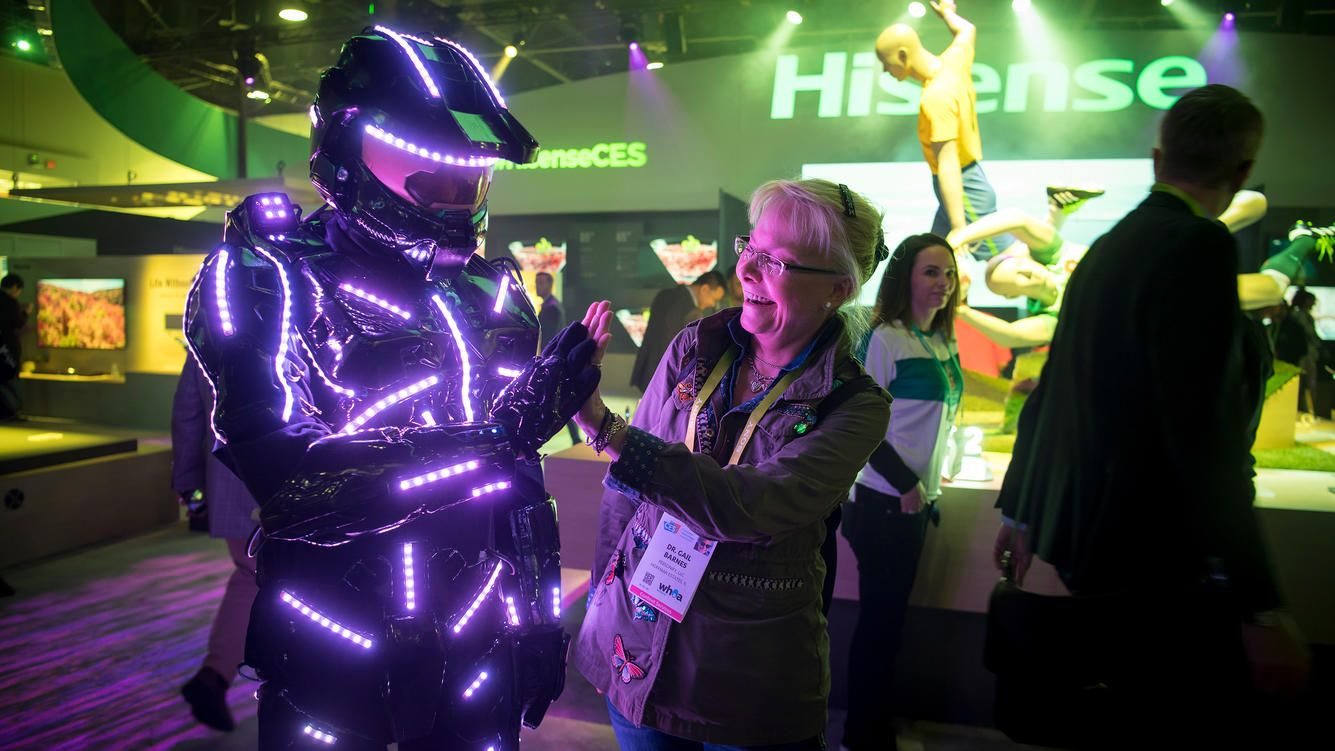 An attendee gives a high-five to a exhibitor wearing a suit with light-emitting diodes (LED) during the 2018 Consumer Electronics Show (CES) in Las Vegas, Nevada, U.S., on Thursday, Jan. 11, 2018.ÊElectric and driverless cars will remain a big part of this year's CES, as makers of high-tech cameras, batteries, and AI software vie to climb into automakers' dashboards. Photographer: David Paul Morris/Bloomberg via Getty Images