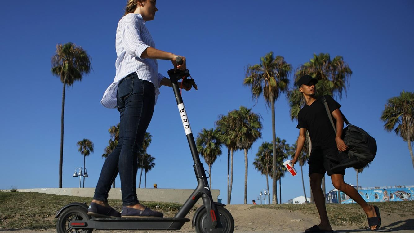 LOS ANGELES, CA - AUGUST 13:  A woman rides a Bird shared dockless electric scooter along Venice Beach on August 13, 2018 in Los Angeles, California. Shared e-scooter startups Bird and Lime have rapidly expanded in the city. Some city residents complain the controversial e-scooters are dangerous for pedestrians and sometimes clog sidewalks. A Los Angeles Councilmember has proposed a ban on the scooters until regulations can be worked out.  (Photo by Mario Tama/Getty Images)