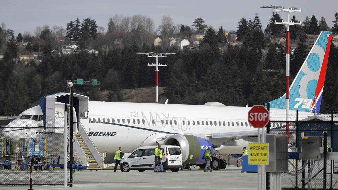 Workers walk next to a Boeing 737 MAX 8 airplane parked at Boeing Field, Thursday, March 14, 2019, in Seattle. The fatal crash Sunday of a 737 MAX 8 operated by Ethiopian Airlines was the second fatal flight for a Boeing 737 Max 8 in less than six months, and more than 40 countries, including the U.S., have now grounded the planes or refused to let them into their airspace. (AP Photo/Ted S. Warren)