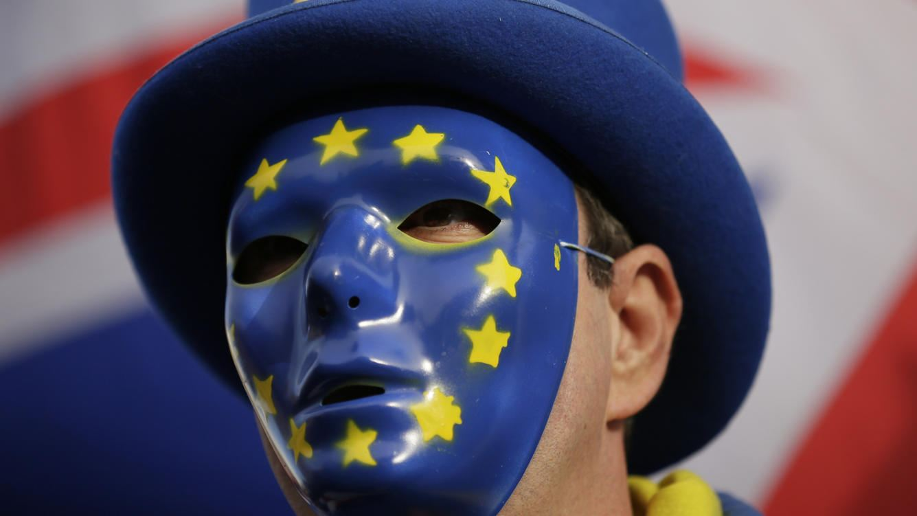An anti-Brexit demonstrator wears a mask bearing the stars of the European flag outside the houses of Parliament in London, Wednesday Dec. 19, 2018. (AP Photo/Tim Ireland)