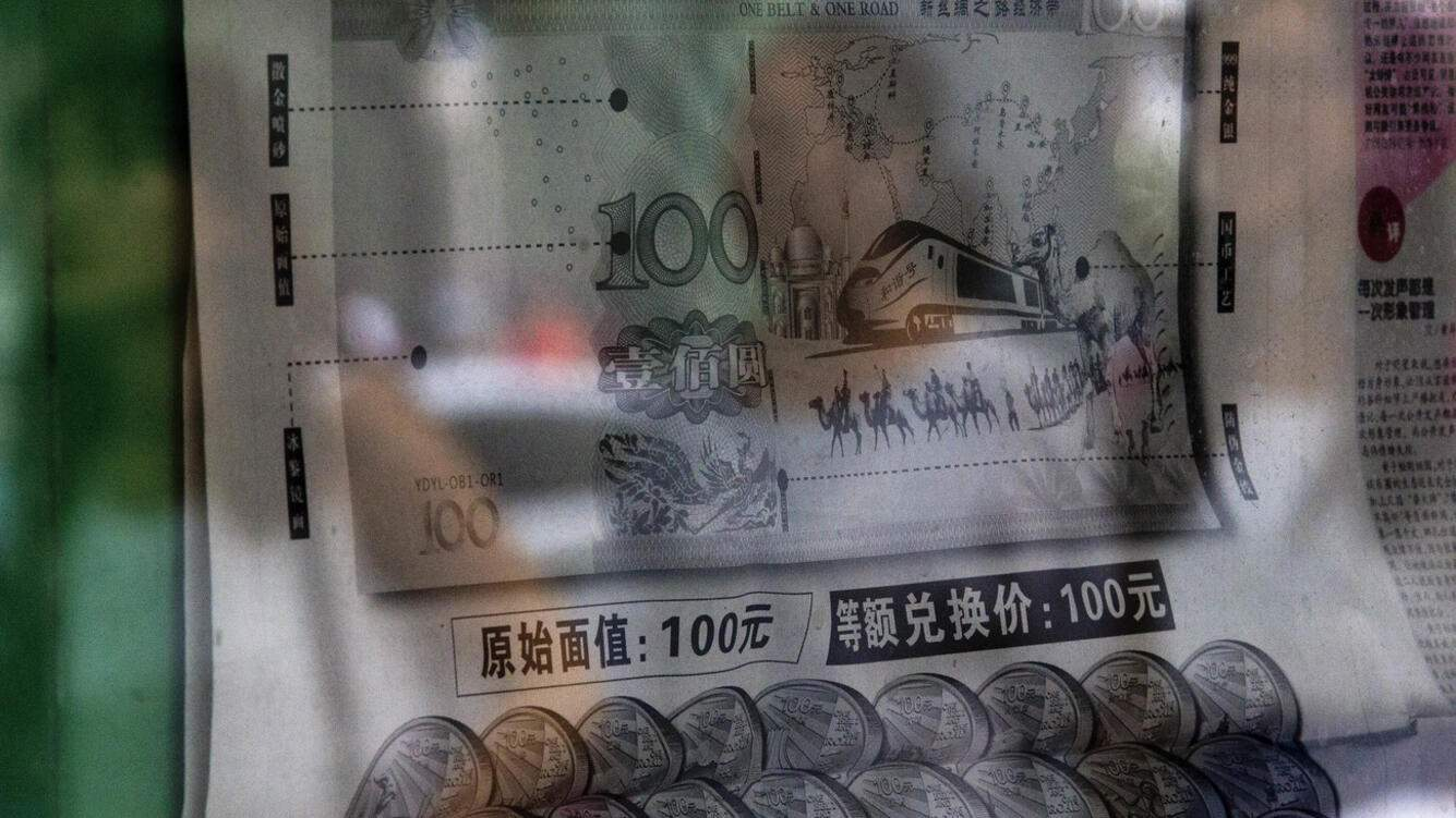 Women is reflected on a glass as they walk past a stand displaying a newspaper reporting that China's central bank or People's Bank of China announced the 2015 edition of the 100 renminbi notes will be issued starting from November 12, in Beijing Tuesday, Aug. 11, 2015. China devalued its tightly controlled currency on Tuesday following a slump in trade, triggering the yuan's biggest one-day decline in a decade. (AP Photo/Andy Wong)