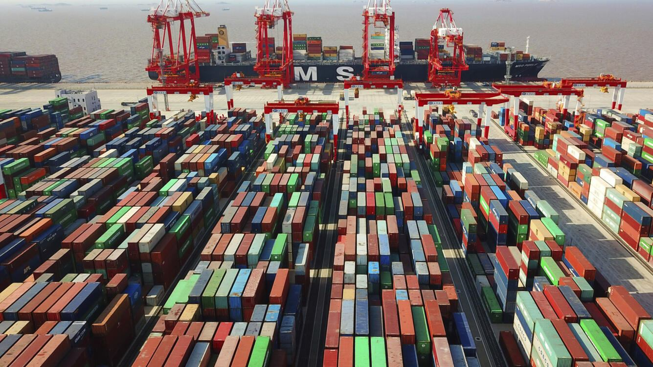 In this April 10, 2018, photo, a cargo ship is docked at the Yangshan container port in Shanghai, China. The Asian Development Bank said in a report Wednesday, April 11 the bank is forecasting that developing Asian economies will expand slightly faster than expected this year but warns U.S. trade tensions are a major risk to its forecast. (Chinatopix via AP)