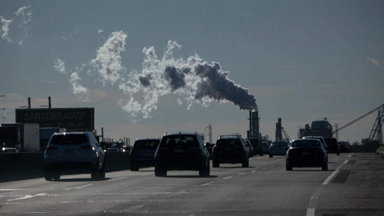 Vehicles move along the The New Jersey Turnpike Way while a Factory emits smoke