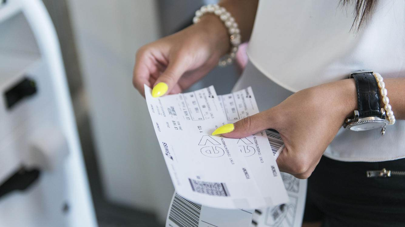 A passenger holds boarding tickets in her hand after a self-check-in in the check-in hall 1 at Zurich Airport, pictured in Kloten, Switzerland, on July 31, 2014. The passenger's name has been electronically removed. (KEYSTONE/Christian Beutler)