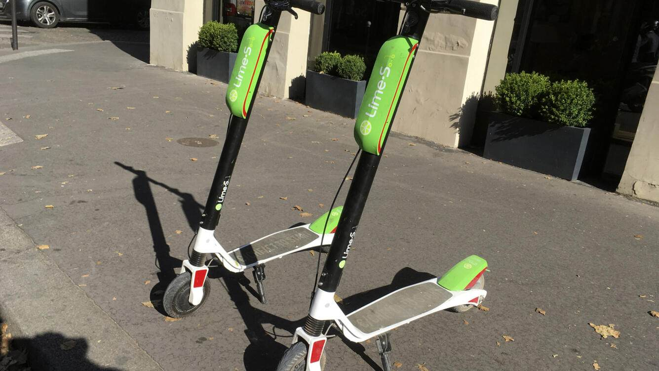 Scooter for sharing park in Paris, Tuesday, July 3, 2018. California-based bicycle sharing service Lime launched a fleet of dock-free electric scooters in Paris. Lime, which operates bike and scooter schemes in about 60 cities and university campuses in the United States, has already launched operations in the German cities of Berlin and Frankfurt and in Zurich, Switzerland. (AP Photo/Michel Euler)