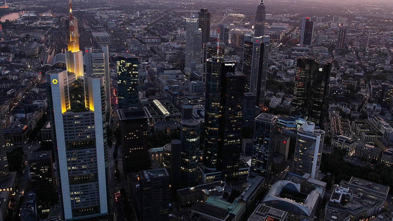 The headquarters of Commerzbank (L) and the twin towers of Deutsche Bank (R) stand illuminated amid the skyline