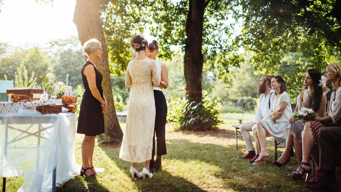 Lesbian couple holding hands in front of the altar. The wedding is outdoors and guest are seated in the foreground.