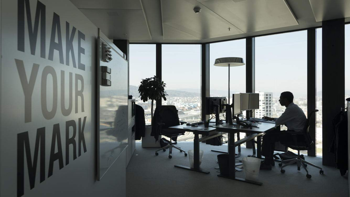 A GAM employee works at his desk in an office at the Prime Tower, a skyscraper, where the pure play asset management group GAM is headquartered, pictured in Zurich, Switzerland, on March 13, 2017. (KEYSTONE/Gaetan Bally)