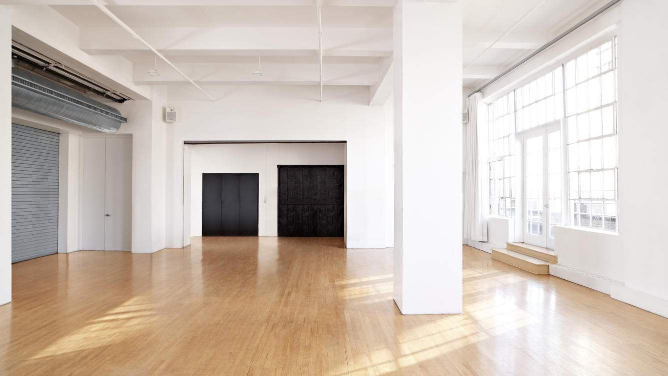 large empty room with cascading sun and open garage door to elevators