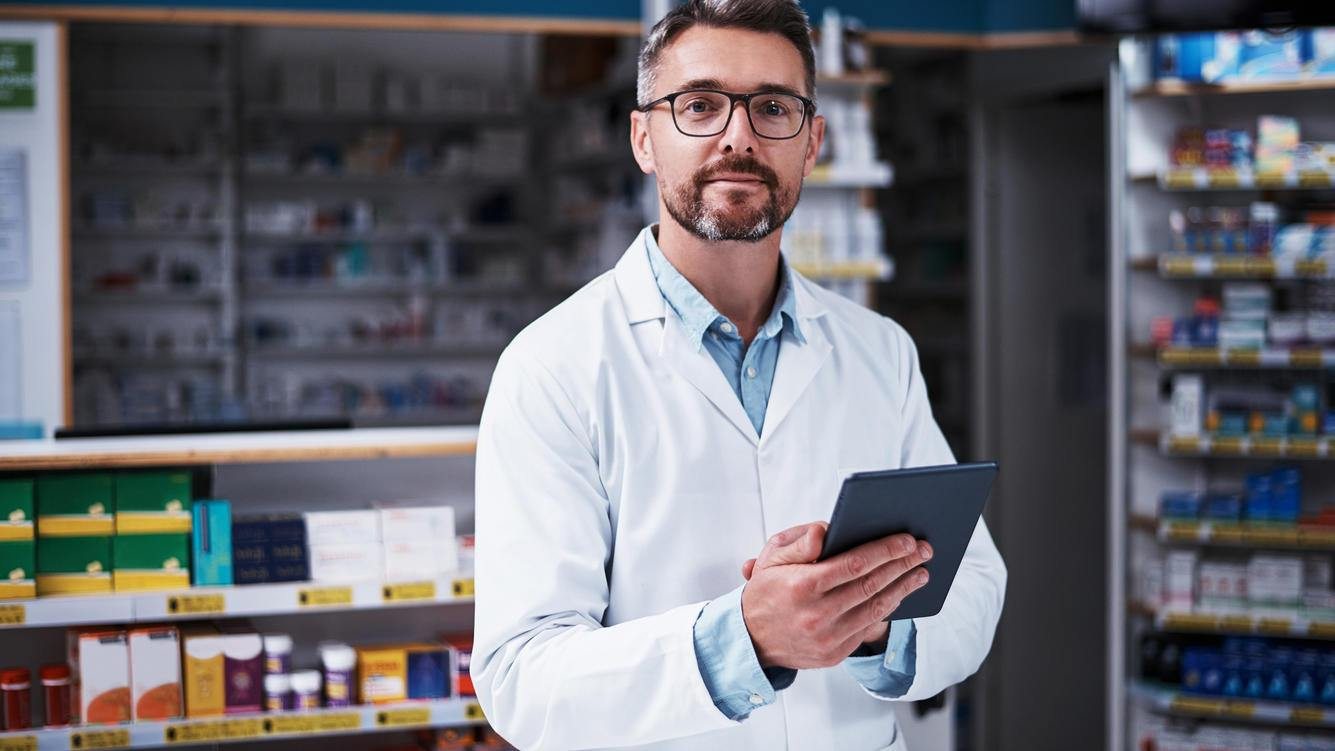 Portrait of a handsome mature pharmacist using a digital tablet in a pharmacy