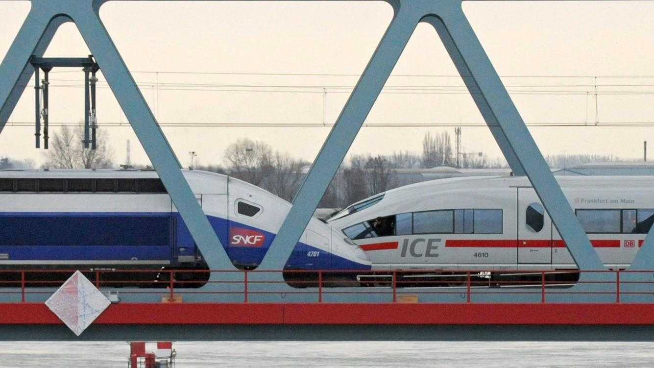 epa02488166 A French TGV train (L) and a German ICE (R) highspeed train meet on the newly inaugurated bridge crossing the river Rhine in Kehl, Germany, 10 December 2010. The bridge is a new connection for highspeed-train between Kehl in Germany and Strasbourg in France. It was finished after three years of construction at some 36 million euro costs.  EPA/MARIJAN MURAT