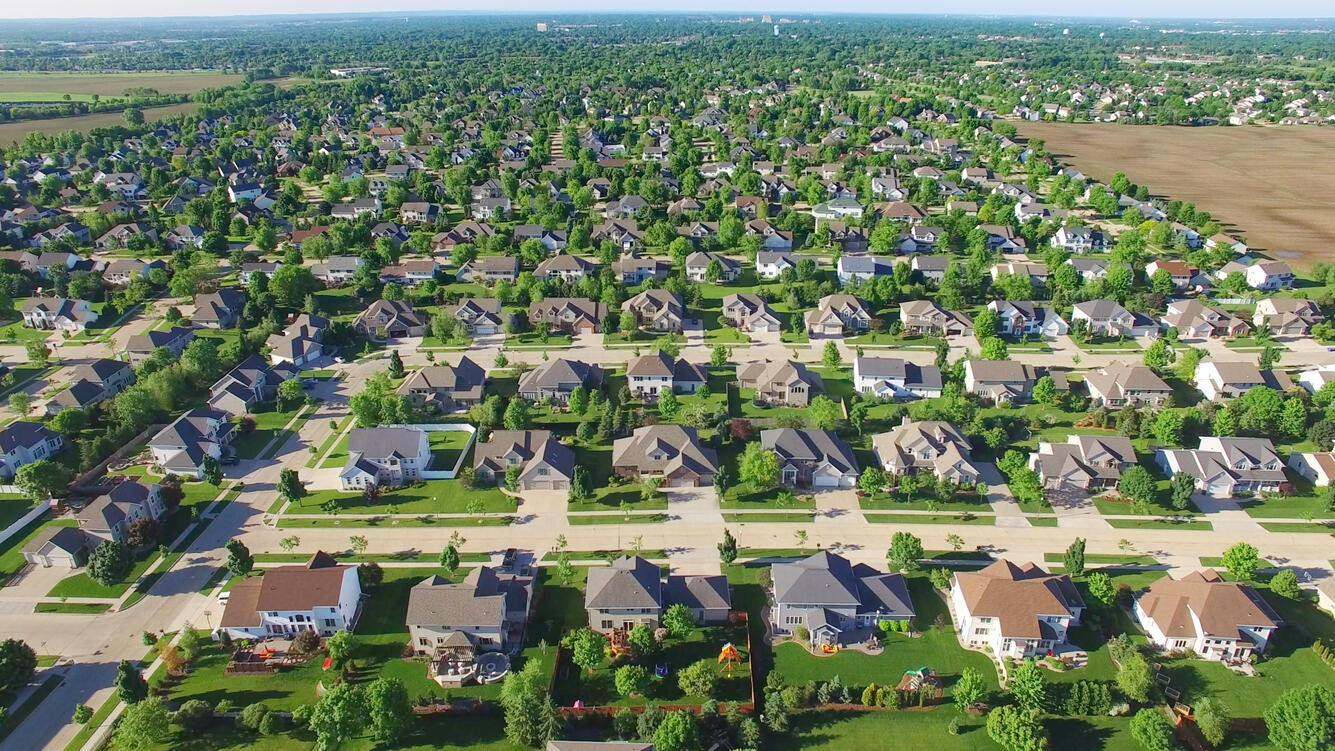 Aerial flyover of beautiful, orderly upper class neighborhood on sunny morning.