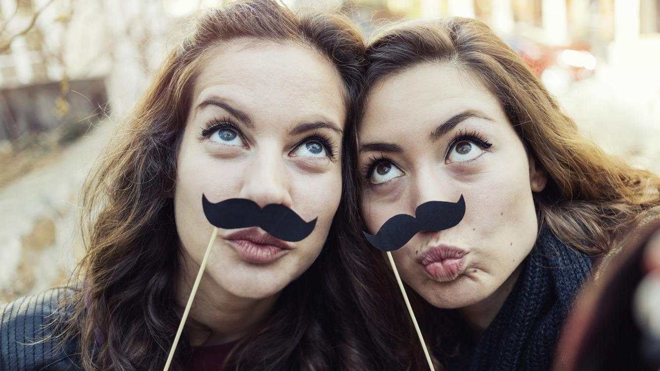 Girls making selfie with fake mustaches