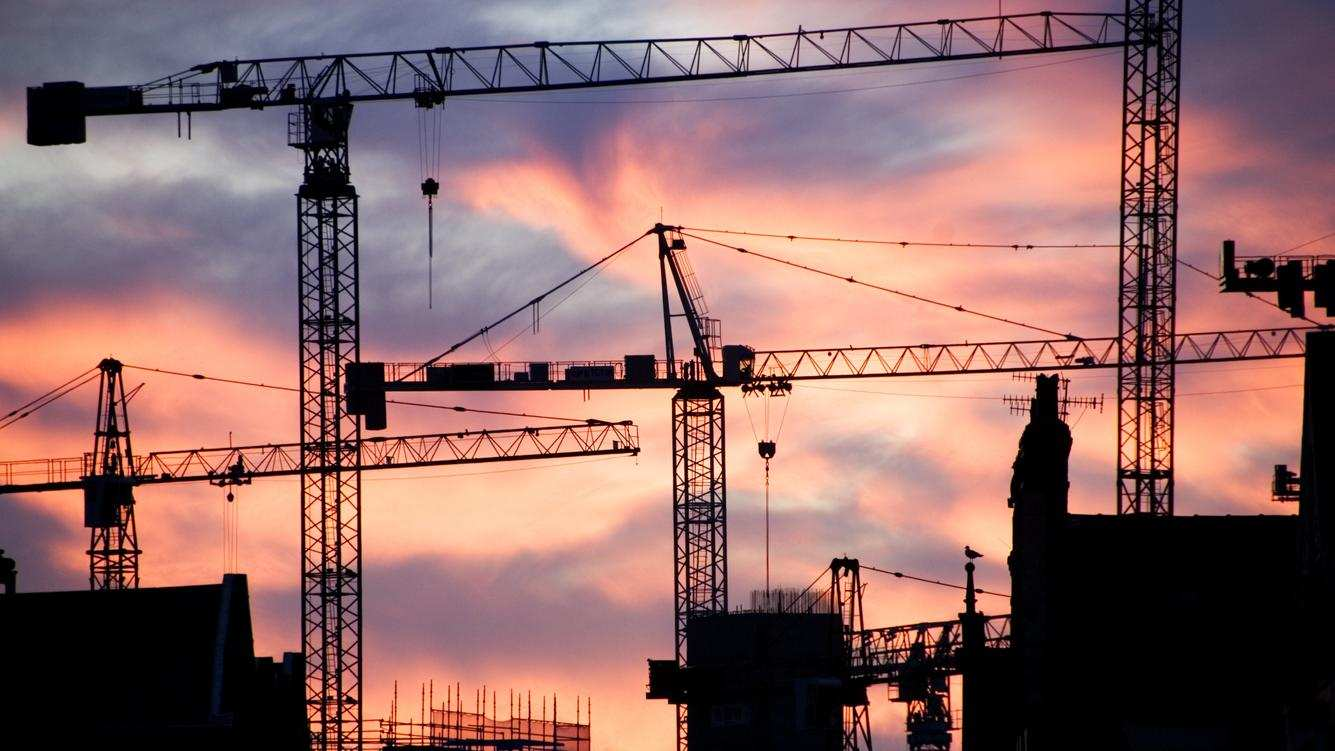 A building site at sunset with cranes silhouetted against a red sky, 2007. Artist: Historic England Staff Photographer. (Photo English Heritage/Heritage Images/Getty Images)