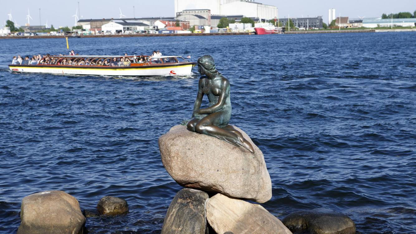 Tourists on a boat watch the Danish popular tourist sight the Little Mermaid statue, created by Edvard Eriksen, in Copenhagen, Denmark, Thursday, May 10, 2018. (KEYSTONE/Salvatore Di Nolfi)
