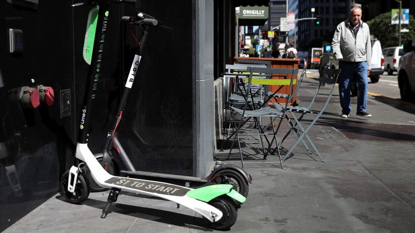 Bird and Lime scooters sit parked in front of a building