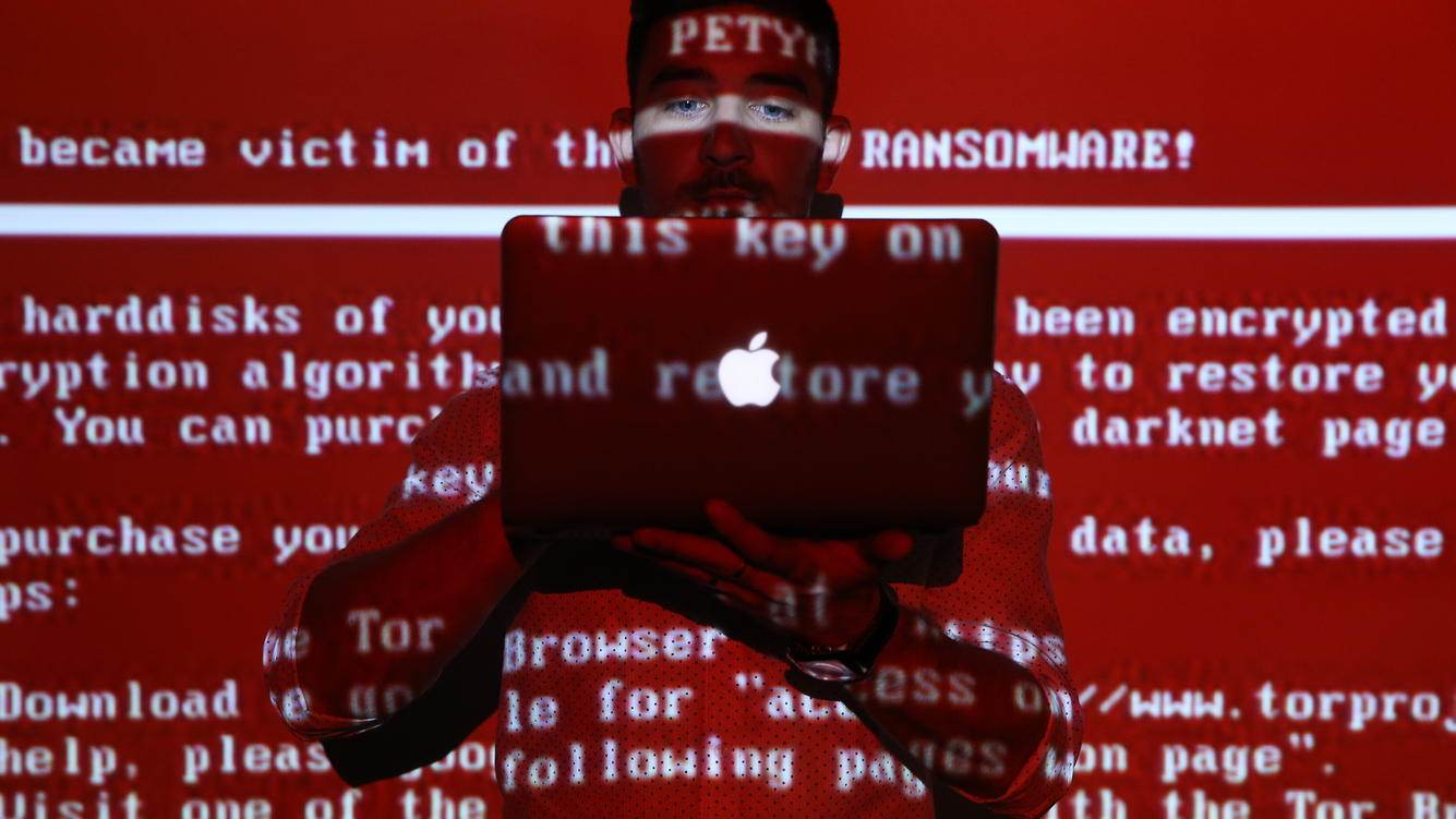 RYAZAN, RUSSIA - JUNE 28, 2017: A message related to the Petya ransomware projected on a young man with a laptop computer; on 27 June 2017 a variant of the Petya ransomware virus hit computers of companies in Russia, Ukraine, and other countries in a cyber attack. Alexander Ryumin/TASS (Photo by Alexander Ryumin\TASS via Getty Images)