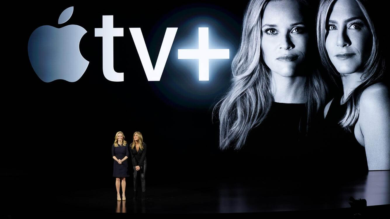Actresses Reese Witherspoon, left, and Jennifer Aniston speak at the Steve Jobs Theater during an event to announce new products Monday, March 25, 2019, in Cupertino, Calif. (AP Photo/Tony Avelar)