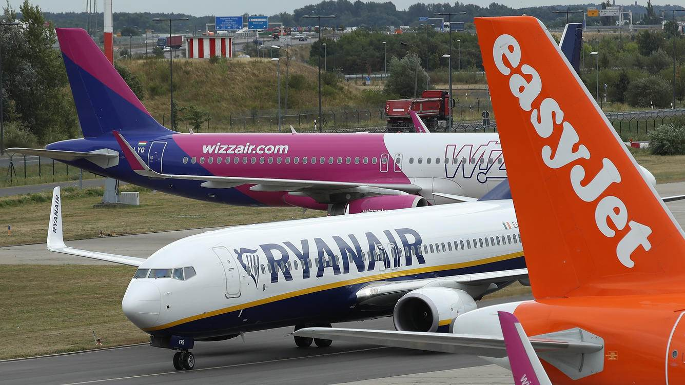 SCHOENEFELD, GERMANY - AUGUST 10:  A RyanAir passenger plane taxis past planes of other discount airliners Wizz Air and EasyJet at Schoenefeld Airport near Berlin during a 24-hour strike by RyanAir pilots on August 10, 2018 in Schoenefeld, Germany. RyanAir pilots in Germany, Ireland, Sweden, Belgium and Holland are taking part in the strike over demands for better pay and working conditions.  (Photo by Sean Gallup/Getty Images)