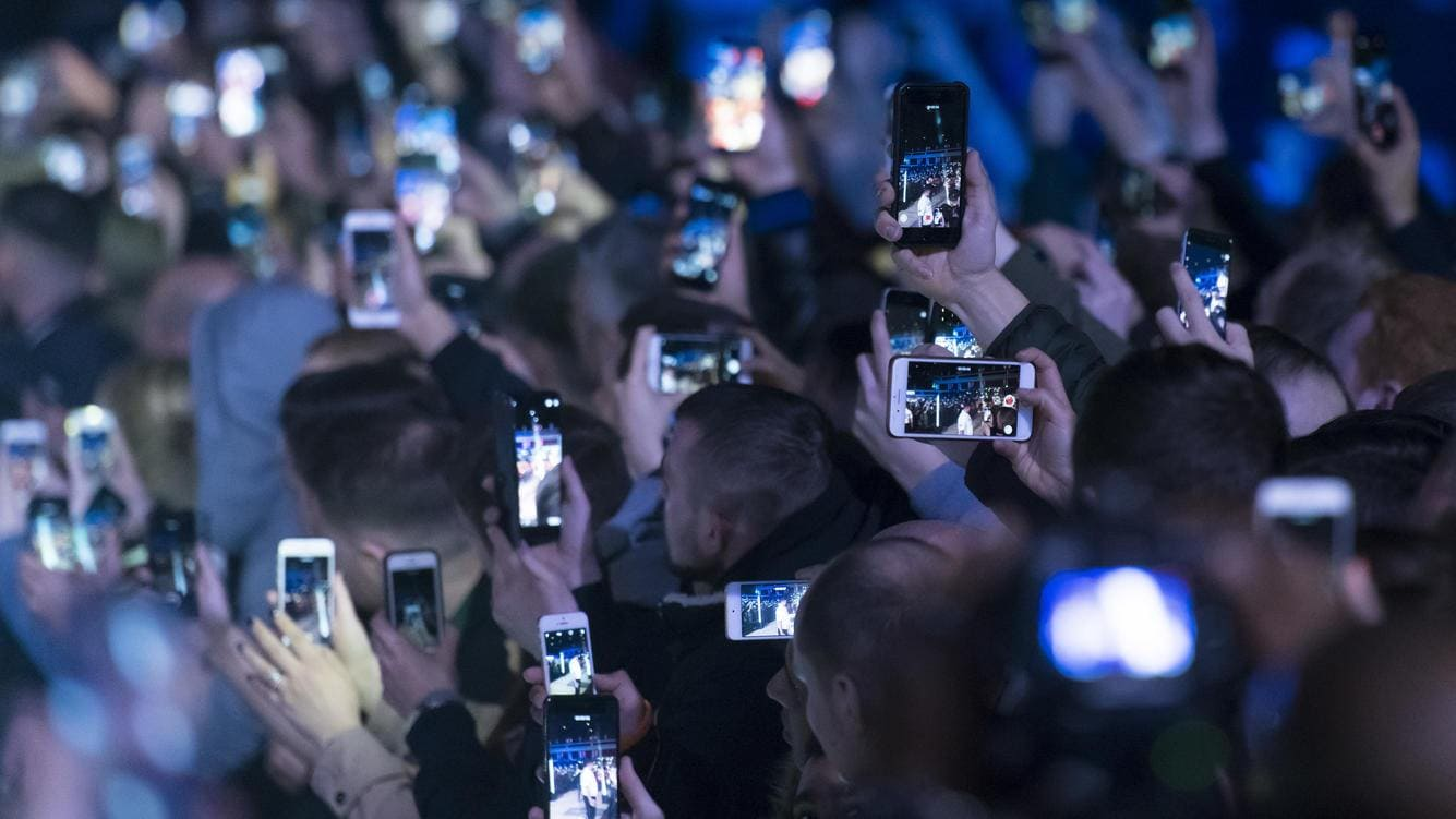 CARDIFF, UNITED KINGDOM - MAY 02: Spectators hold up mobile phones at an event on May 2, 2018 in Cardiff, United Kingdom. (Photo by Matthew Horwood/Getty Images)