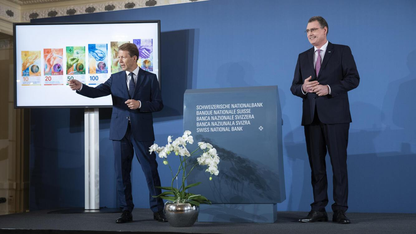 Fritz Zurbruegg, Vice president of the Swiss National Bank, left, and Thomas Jordan, President of the Swiss National Bank, answer questions beside a screen showing the new series of Swiss banknotes during the presentation of the new Swiss 100 francs banknote in Bern, Switzerland, Tuesday, September 3, 2019. (KEYSTONE/Peter Klaunzer)