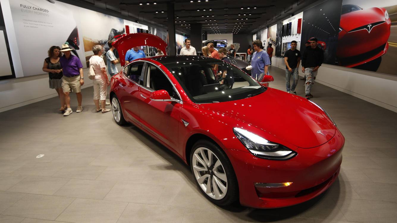 FILE- In this July 6, 2018, file photo prospective customers confer with sales associates as a Model 3 sits on display in a Tesla showroom in the Cherry Creek Mall in Denver. Tesla Inc. reports earnings on Wednesday, Oct. 24. (AP Photo/David Zalubowski, File)