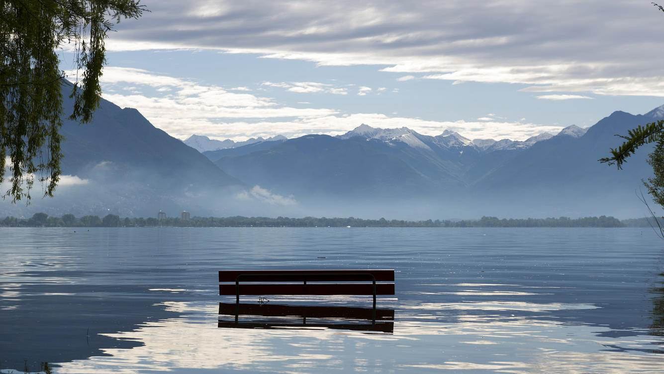 Bench with tree branch on a flooding alpine lake Maggiore with snow-capped mountain in background in Locarno, Switzerland.